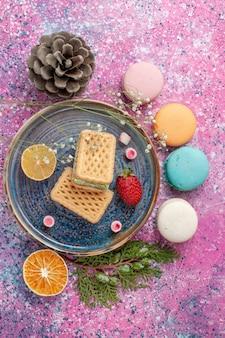 Vista superior de deliciosos macarons franceses com waffles na mesa rosa