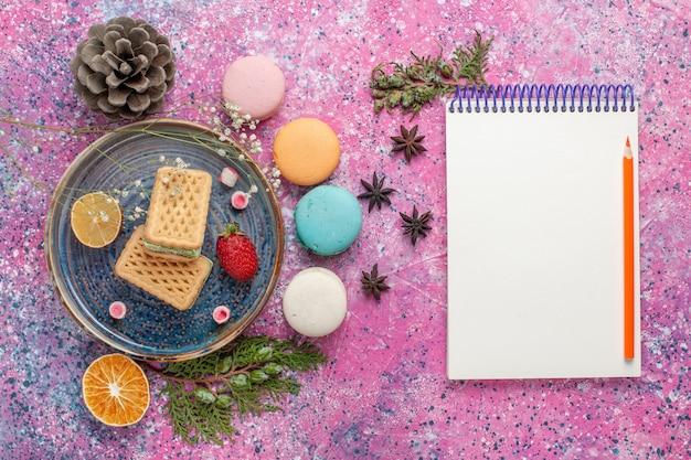Vista superior de deliciosos macarons franceses com waffles na superfície rosa
