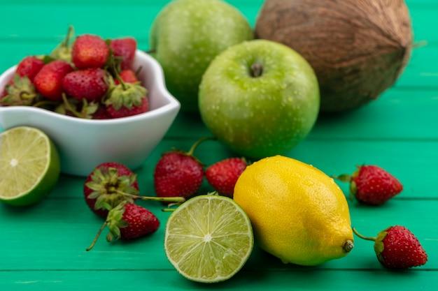 Vista superior de deliciosos morangos em uma tigela branca com coco e limão em um fundo verde de madeira