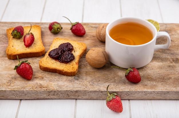 Vista superior de deliciosos morangos no pão com uma xícara de chá com limão em uma placa de cozinha de madeira em um fundo branco de madeira