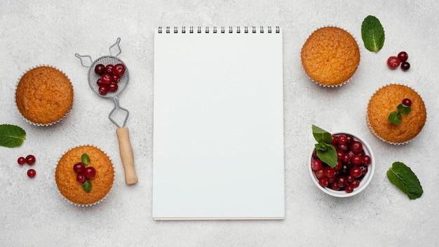 Vista superior de deliciosos muffins com frutas e caderno