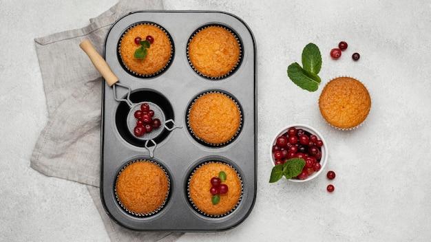 Vista superior de deliciosos muffins em uma assadeira com frutas vermelhas