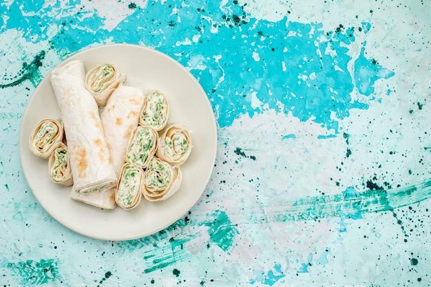 Vista superior de deliciosos pãezinhos de vegetais inteiros e fatiados no piso azul brilhante, pão de refeição, lanche vegetal