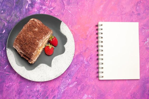Vista superior de deliciosos pãezinhos doces com morangos na superfície rosa