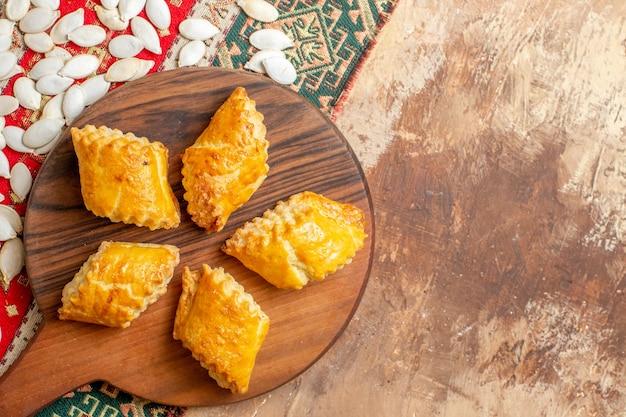 Vista superior de deliciosos pastéis de nozes com sementes em um fundo marrom
