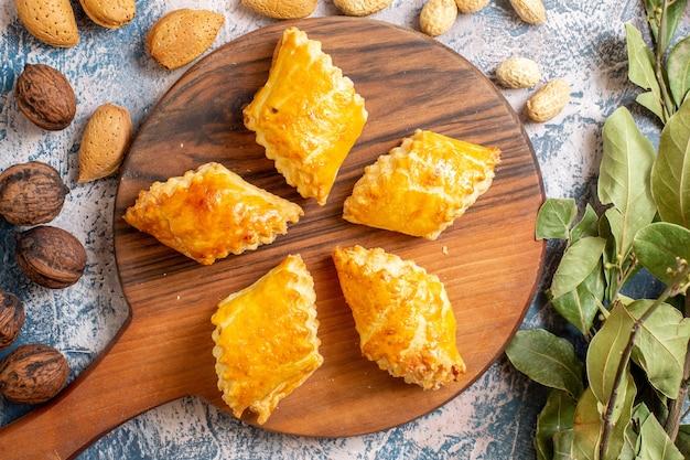 Vista superior de deliciosos pastéis doces com nozes na superfície azul