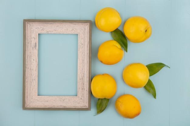 Vista superior de deliciosos pêssegos amarelos frescos isolados em um fundo azul com espaço de cópia