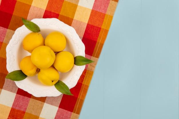 Vista superior de deliciosos pêssegos frescos e amarelos em uma tigela branca em um pano xadrez em um fundo azul com espaço de cópia