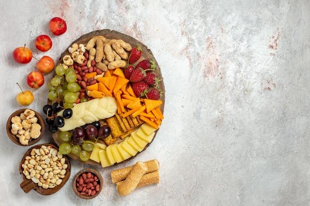 Vista superior de deliciosos petiscos cips, uvas, queijo e nozes em uma superfície branca clara