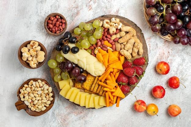 Vista superior de deliciosos petiscos cips uvas, queijo e nozes na superfície branca