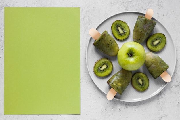 Vista superior de deliciosos picolés com maçãs e copie o espaço