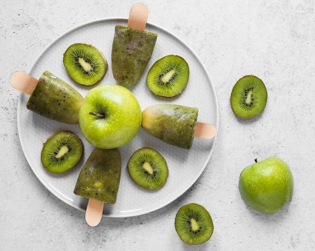 Vista superior de deliciosos picolés com maçãs e kiwi