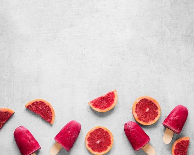 Vista superior de deliciosos picolés com toranja vermelha e espaço de cópia
