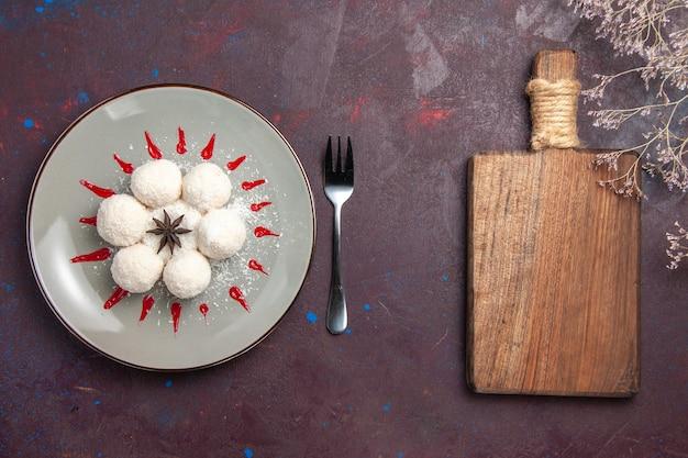 Vista superior de deliciosos rebuçados de coco redondo formado com glacê vermelho sobre preto