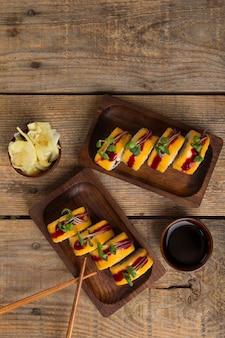 Vista superior de deliciosos rolos de sushi com ingredientes na mesa de madeira