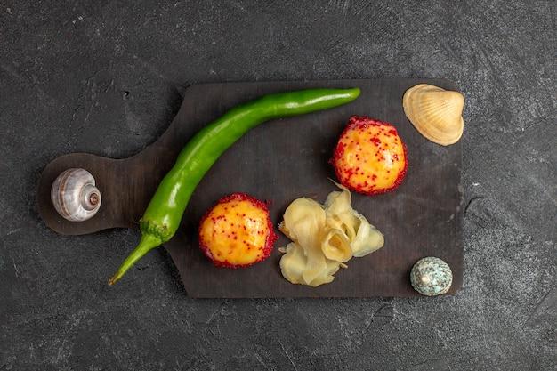 Vista superior de deliciosos rolos de sushi de peixe com peixe e arroz junto com pimenta verde na parede cinza