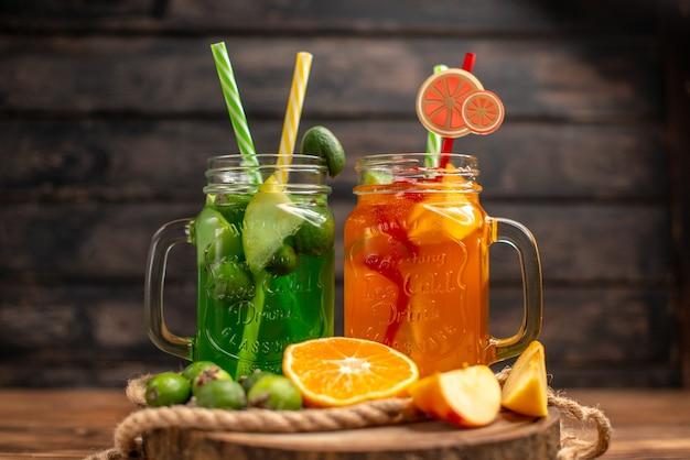 Vista superior de deliciosos sucos de frutas frescos servidos com maçã e laranjas feijoas em uma tábua de madeira