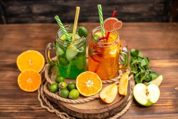 Vista superior de deliciosos sucos frescos e frutas em uma bandeja de madeira sobre um fundo marrom