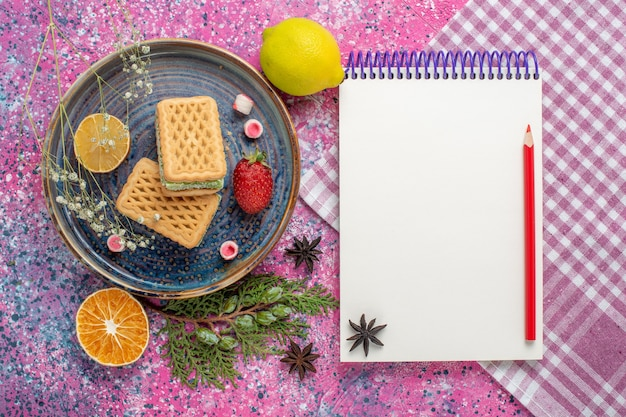 Vista superior de deliciosos waffles com bloco de notas na superfície rosa claro