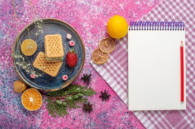Vista superior de deliciosos waffles com bloco de notas na superfície rosa
