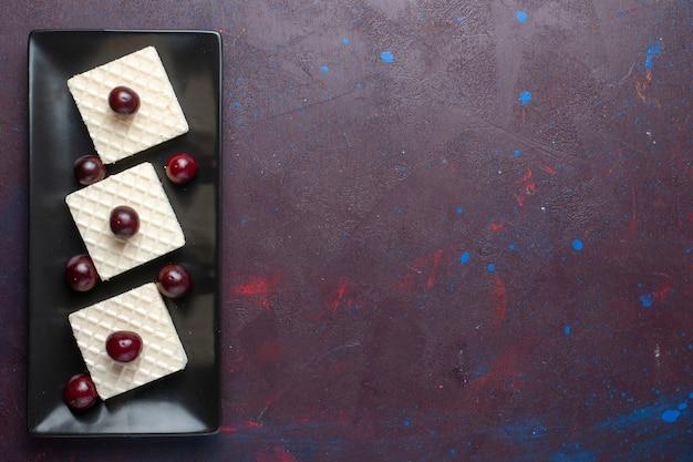 Vista superior de deliciosos waffles com cerejas dentro de um prato escuro na superfície escura