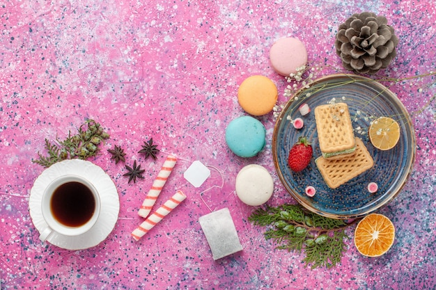 Vista superior de deliciosos waffles com deliciosos macarons franceses e chá na mesa rosa