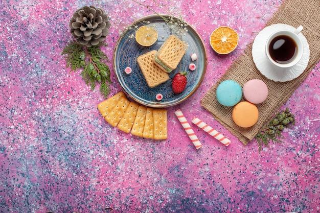 Vista superior de deliciosos waffles com macarons franceses e chá na superfície rosa