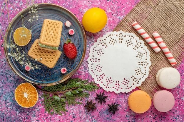 Vista superior de deliciosos waffles com macarons franceses na superfície rosa claro