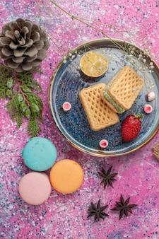 Vista superior de deliciosos waffles com macarons franceses na superfície rosa