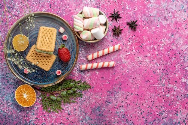 Vista superior de deliciosos waffles com marshmallow na superfície rosa