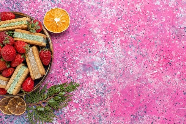 Vista superior de deliciosos waffles com morangos vermelhos frescos na superfície rosa