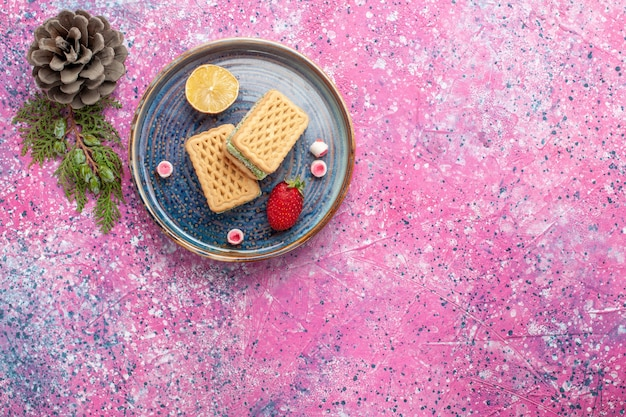 Vista superior de deliciosos waffles com superfície rosa morango