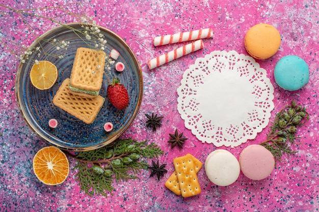 Vista superior de deliciosos waffles com uma xícara de chá e macarons na superfície rosa