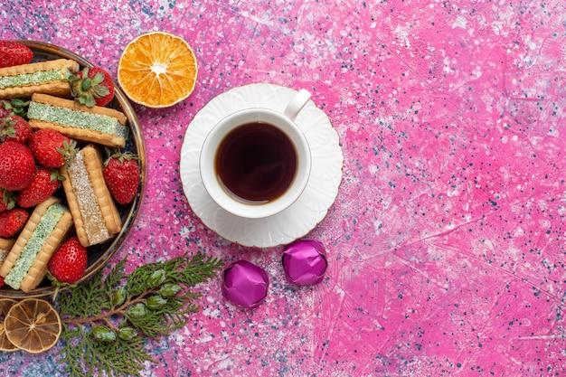 Vista superior de deliciosos waffles com uma xícara de chá e morangos vermelhos frescos na superfície rosa