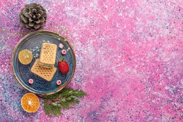 Vista superior de deliciosos waffles na superfície rosa