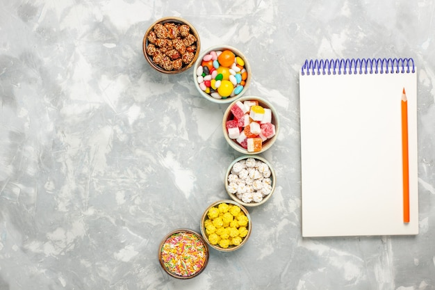 Vista superior de diferentes balas doces com marshmallows e bloco de notas na superfície branca
