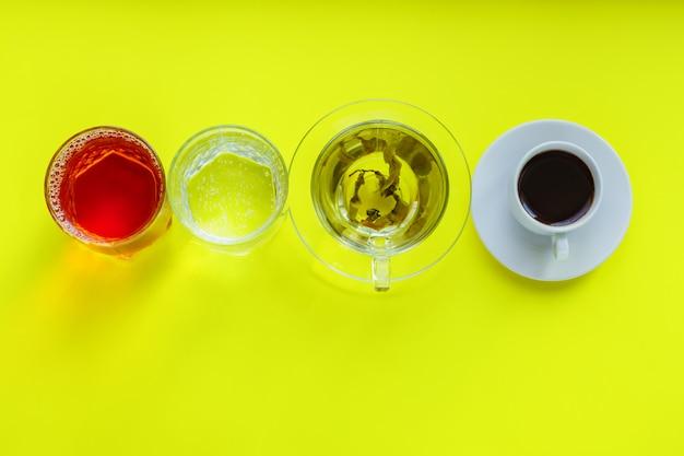 Vista superior de diferentes bebidas - beber café, água com gás, suco de maçã e chá verde em backgeound amarelo. vida saudável e conceito de dieta