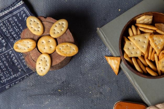 Vista superior de diferentes biscoitos salgados no fundo cinza.