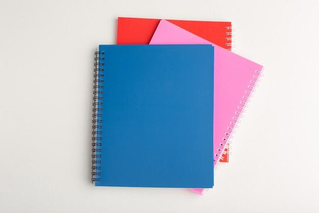 Vista superior de diferentes cadernos coloridos na superfície branca