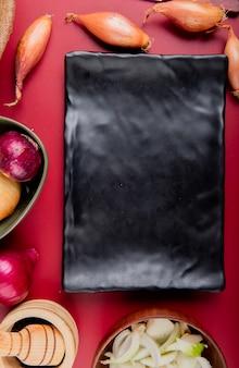 Vista superior de diferentes cebolas inteiras e fatiadas e pimenta preta no triturador de alho ao redor do prato na superfície vermelha
