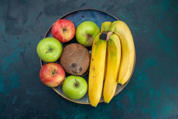 Vista superior de diferentes composições de frutas, coco, maçãs e bananas, na mesa azul escuro