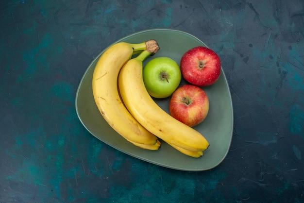 Vista superior de diferentes composições de frutas, maçãs e bananas, na mesa azul escura