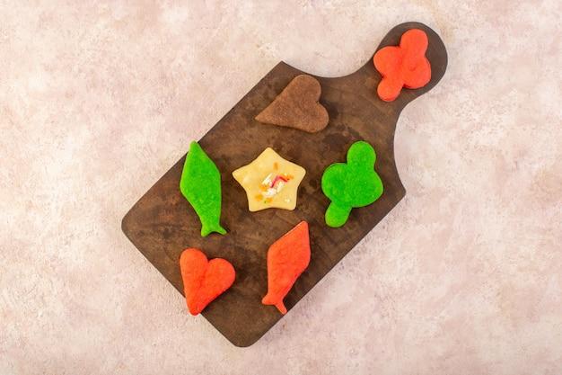 Vista superior de diferentes deliciosos biscoitos coloridos formados na mesa de madeira marrom