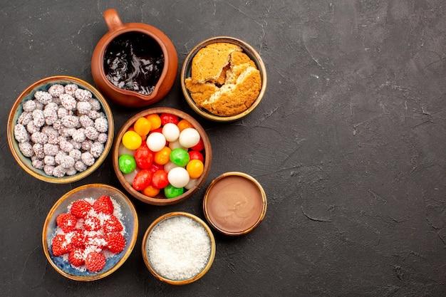 Vista superior de diferentes doces coloridos com confitures em uma superfície escura de biscoito de chá doce