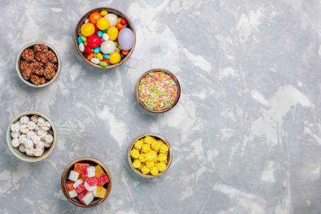 Vista superior de diferentes doces coloridos com geleia na mesa branca