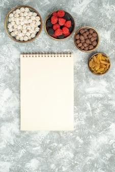 Vista superior de diferentes doces com o bloco de notas na mesa de trabalho leve doce açúcar chá doce cookie