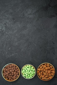 Vista superior de diferentes doces de açúcar dentro de pequenos potes em preto