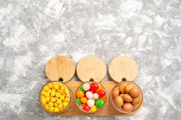 Vista superior de diferentes doces, doces coloridos na superfície branca