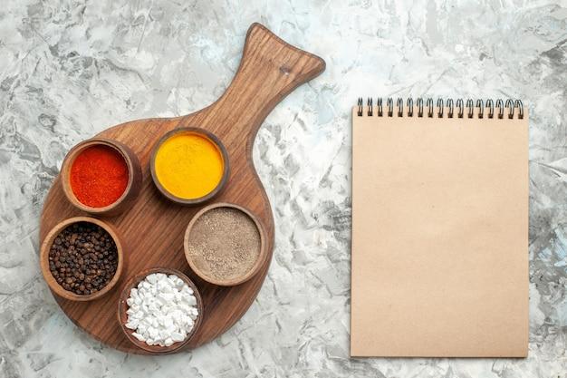 Vista superior de diferentes especiarias na tábua e caderno em fundo branco