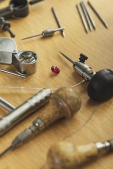 Vista superior de diferentes ferramentas de gravador de ourives no local de trabalho de joias. área de trabalho para confecção de joias artesanais com ferramentas profissionais. ferramentas sobre fundo de madeira rústico.